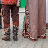 Detaljer av de Bashkir traditionella nationella kläderen Män piskar kängor med applikationer och botten av kvinnors klänningwi arkivbilder