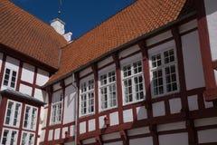 Detaljer av den gamla halvan timrade byggnad med röda tegelplattor och casematefönster Royaltyfri Fotografi