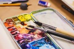 Detaljer av den idérika processen av konstnären, en palett med vattenfärgmålarfärger, borstar och kanfas med en skissa Arkivbild