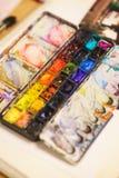 Detaljer av den idérika processen av konstnären, en palett med vattenfärgmålarfärger, borstar och kanfas med en skissa Arkivbilder