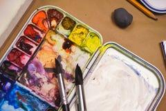Detaljer av den idérika processen av konstnären, en palett med vattenfärgmålarfärger, borstar och kanfas med en skissa Royaltyfri Bild
