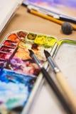 Detaljer av den idérika processen av konstnären, en palett med vattenfärgmålarfärger, borstar och kanfas med en skissa Royaltyfria Foton
