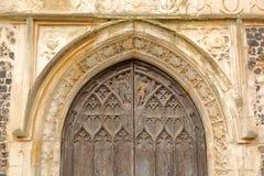 Detaljer av ingången till kyrkan av St Michael Coslany med anmärkningsvärd skärm av flinta och stenhuggeriarbetet för 15th århund Royaltyfri Fotografi