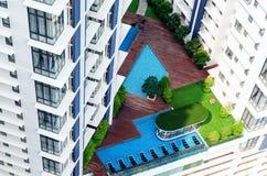 Detaljer av modern byggnadsyttersida - uteplats i höghus med simbassängen, vardagsrumzon, gröna träd Arkivfoton