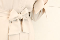Detaljer av pilbågebältebandet i beige kvinnaklänningdräkt utformar fashion moderiktigt arkivbilder