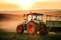 Detaljer av traktoren, bonde som arbetar i fälten med traktoren på en solnedgångbakgrund Åkerbruka branschdetaljer arkivbild