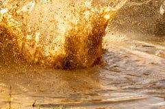 Detaljer av vattendroppar i gyttja från en färgstänk i en pöl i ett hinderlopp arkivbilder