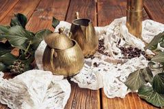 Detaljer fångade en mässing mjölkar tillbringaren och en mässingssockerbunke, murgröna på en gammal trätabellöverkant med kaffebö arkivfoton
