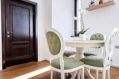 Detaljer för inredesign - modernt möblemang som äter middag tabellen med stolar i kök arkivbild