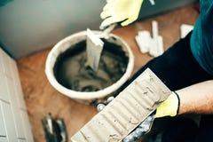 Detaljer för keramiska tegelplattor Slut för renovering för inredesign upp Arbetare som tillfogar bindemedel på keramiska tegelpl Royaltyfria Bilder