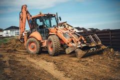 Detaljer för konstruktionsplats med backhoen rullar jord och jord för laddare rörande Arkivfoton