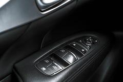 Detaljer för svart perforerat läder för bil inre av dörrhandtaget med fönsterstyrning och justeringar Bildörrhandtag inom luxen Royaltyfri Fotografi