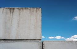 Detaljerad bakgrund av betongväggfototextur på blå härlig himmelbakgrund med vita moln royaltyfri bild