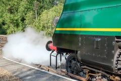 Detaljerad främre sikt av en berömd brittisk visning för ångalokomotiv som låter av ånga medan på en järnvägsstation royaltyfri bild