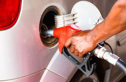 Detaljhand av arbetarmannen som tankar bilen på bensinstationen Begreppsfoto för bruk av fossil- bränslen bensin, dieselmotor arkivbild