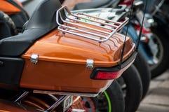 Detaljhandel av apelsinöverkantfallet på den Harley Davidson mopeden som parkeras i gatan Arkivfoto