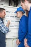 Detaljhandlare och lärlingar som installerar fördelningsbrädet Royaltyfri Bild