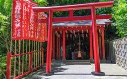 Detaljsikt på en traditionella röda Torii och en japansk Jigoku Meguri Shinto relikskrin som inramas av flaggor och grönt land fotografering för bildbyråer