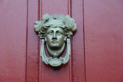 Detalle artístico en golpeador elaborado en la puerta roja del hogar foto de archivo