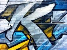 Detalle azul y amarillo de la pintada en una pared de ladrillo Fotos de archivo