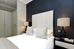 Detalle contemporáneo del dormitorio con la cama gigante con el desig de lujo Imagen de archivo libre de regalías