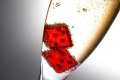 Detalle de dados rojos en una flauta con las burbujas del oro Foto de archivo