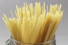 Detalle de espaguetis en un tarro de cristal en fondo gris Fotografía de archivo