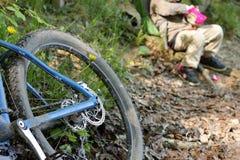 Detalle de la bici de montaña azul en bosque con el niño de reclinación imagenes de archivo