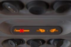 Detalle de la cabina del aeroplano, segnal sengal del cinturón de no fumadores y de seguridad foto de archivo