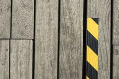 Detalle de la calzada peatonal de madera y de una cinta negra y amarilla Imagen de archivo