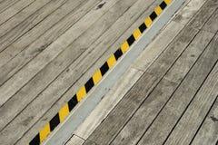 Detalle de la calzada peatonal de madera y de una cinta negra y amarilla Imagen de archivo libre de regalías