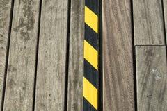 Detalle de la calzada peatonal de madera y de una cinta negra y amarilla Foto de archivo