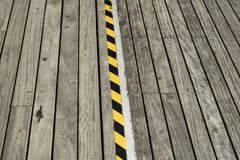 Detalle de la calzada peatonal de madera y de una cinta negra y amarilla Fotos de archivo libres de regalías