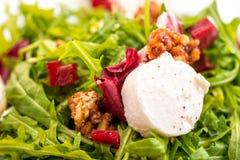 Detalle de la ensalada fresca del arugula con remolachas, queso de cabra y nueces en la placa de cristal en el fondo blanco, phot Foto de archivo