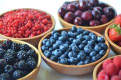 Detalle de la fruta y de las bayas frescas del verano en cuencos de madera foto de archivo libre de regalías