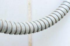 Detalle de la manguera de ducha calcificada sucia con del limescale o de la cal en ella, cierre la escala para arriba foto de archivo