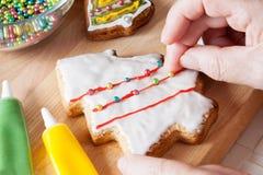Detalle de la mano de la mujer que adorna la galleta de la Navidad Foco selectivo Imagen de archivo libre de regalías