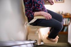 Detalle de la mujer mayor que se sienta en la elevación de la escalera en casa para ayudar a movilidad imagen de archivo