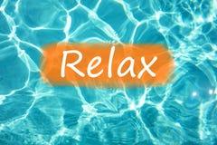 Detalle de la palabra y de x22; Relax& x22; en el agua y el sol de la piscina que reflejan en la superficie Fotos de archivo libres de regalías