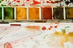 Detalle de la paleta de la acuarela que muestra las medias cacerolas de rojo, de ocre, y el verde foto de archivo