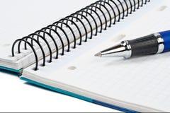 Detalle de la pluma y de la hoja en blanco del cuaderno Foto de archivo