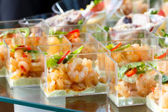 Detalle de la tabla de comida fría con canapes de la gamba en platos plásticos Imagenes de archivo