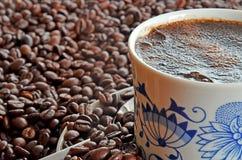 Detalle de la taza de café y de la pila de granos de café Imagen de archivo