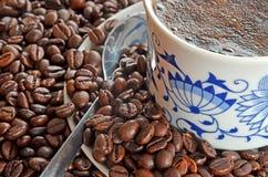 Detalle de la taza de café y de la pila de granos de café Imagenes de archivo