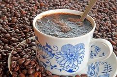 Detalle de la taza de café y de la pila de granos de café Fotografía de archivo libre de regalías