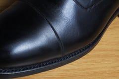 Detalle de la vista lateral de un zapato clásico de cuero negro en una sala de baile de madera Foto de archivo libre de regalías