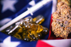Detalle de las cápsulas del aceite del cáñamo CBD y brote delante del americano foto de archivo libre de regalías