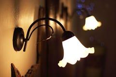 Detalle de las lámparas del vintage colocadas sobre una cama de un cuarto de lujo en un hotel de la cabaña del país cerca de Giro Fotos de archivo libres de regalías