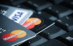 Detalle de las tarjetas de crédito encima de una foto de la macro del teclado del ordenador portátil Imagenes de archivo