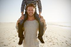 Detalle de los hombros de Carrying Son On del padre en la playa del invierno fotos de archivo libres de regalías